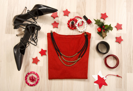 Winter Christmas sweater with accessories arranged on the floor. Woman red outfit with matching necklace, bracelet and nail polish lied down. Stockfoto