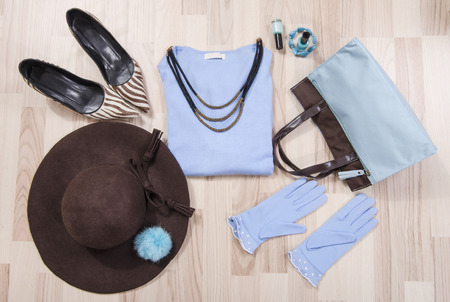 lied: Winter sweater and accessories arranged on the floor. Woman blue and brown accessories, high heels, hat, necklace and gloves lied down. Stock Photo