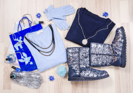 lied: Winter Christmas sweaters and sparkly boots with accessories arranged on the floor. Woman blue outfit with matching sequins boots, gloves and necklace lied down.