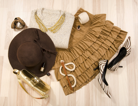 leather skirt: Winter sweater and leather skirt with accessories arranged on the floor. Woman brown outfit with matching hat, necklace, belt and purse lied down.