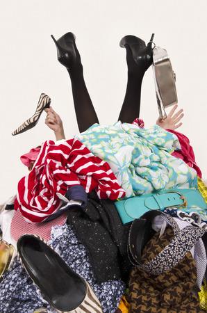 Les jambes de la femme et de mains tendues à partir d'un gros tas de vêtements et accessoires. Femme ensevelie sous une femme encombré placard en désordre. Femme en talons hauts besoin de l'aide à beaucoup de shopping. fille shopaholic. Banque d'images - 49766112