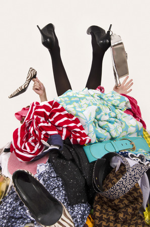 Woman legs and hands reaching out from a big pile of clothes and accessories. Woman buried under an untidy cluttered woman wardrobe. Woman in high heels needs help from to much shopping. Shopaholic girl.