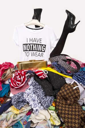 Woman legs reaching out from a big pile of clothes with a t-shirt saying nothing to wear. Woman buried under an untidy cluttered woman wardrobe. Woman in high heels needs help from to much shopping. Shopaholic girl.