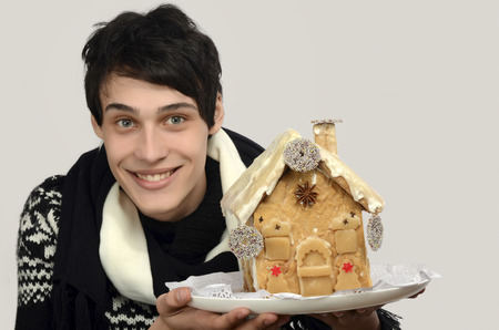 man made: Happy man holding a gingerbread house. Man smiling celebrating Christmas with a home made gingerbread house. Stock Photo