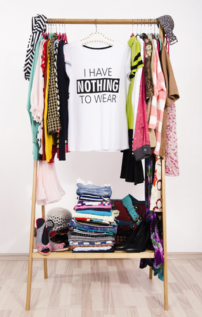 heap: Many clothes on the rack with a t-shirt saying nothing to wear. Close up on a cluttered wardrobe with colorful clothes and accessories, many clothes and nothing to wear.