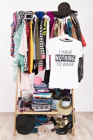 Veel kleren op het rek met een t-shirt te zeggen niets te dragen. Close-up op een rommelige kast met kleurrijke kleding en accessoires, veel kleren en niets om te dragen.