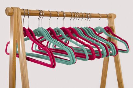 Rack of clothes with empty hangers. Close up on colorful pink and green felt hangers.