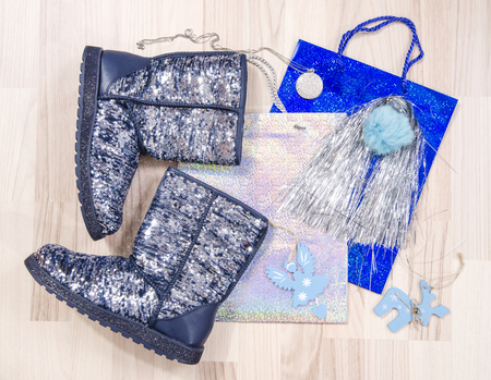Winter Christmas sparkly boots with accessories arranged on the floor. Woman blue festive sequins boots lied down on shopping bags. Stock Photo