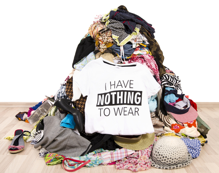 the thrown: Big pile of clothes thrown on the ground with a t-shirt saying nothing to wear. Close up on a untidy cluttered wardrobe with colorful clothes and accessories, many clothes and nothing to wear.