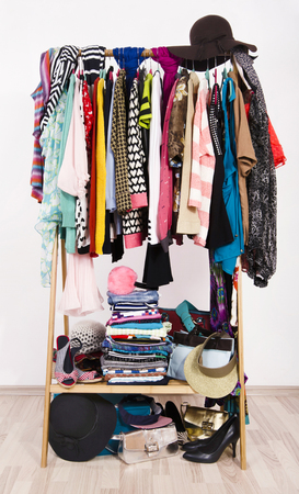 clothes rack: Many colorful clothes on hangers in a store. A lot of clothes and accessories hanging on a rack nicely arranged on hangers and in piles. Stock Photo