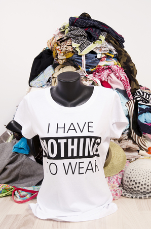 untidy: Big pile of clothes thrown on the ground with a t-shirt saying nothing to wear. Close up on a untidy cluttered wardrobe with colorful clothes and accessories, many clothes and nothing to wear top on a mannequin.