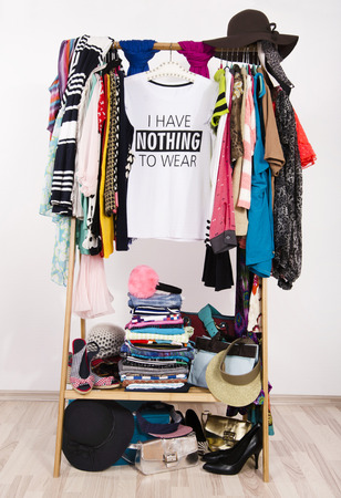 clothing: Many clothes on the rack with a t-shirt saying nothing to wear. Close up on a cluttered wardrobe with colorful clothes and accessories, many clothes and nothing to wear.