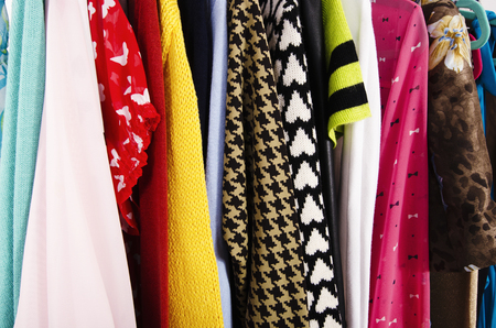 clothes rack: Close up on colorful clothes on hangers in a store. Clothes and accessories hanging on a rack nicely arranged. Stock Photo