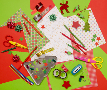 craft supplies: Arts and craft supplies for Christmas. Red and green color paper, pencils, different washi tapes, craft scissors, festive xmas supplies for decoration. Stock Photo