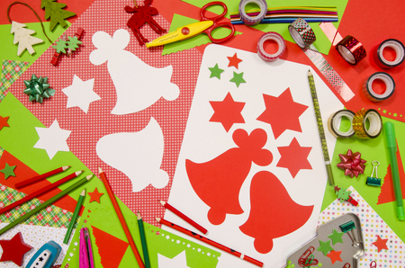 craft supplies: Arts and craft supplies for Christmas. Red and green color paper, pencils, different washi tapes, craft scissors, cardboard bell cut and decorations.