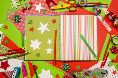 craft supplies: Arts and craft supplies for Christmas. Red and green color paper, pencils, different washi tapes, craft scissors, scrapbook agenda and decorations. Stock Photo