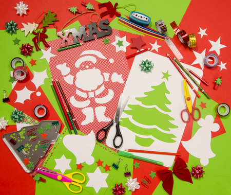 table scraps: Arts and craft supplies for Christmas. Red and green color paper, pencils, different washi tapes, craft scissors, cardboard Santa and Christmas tree cut and decorations.
