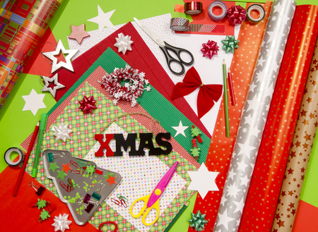 craft supplies: Arts and craft supplies for Christmas. Arts and craft supplies for Christmas. Colorful wrapping paper rolls, pencils, different washi tapes, craft scissors, xmas sign, Wrapping Christmas gifts in colorful paper.