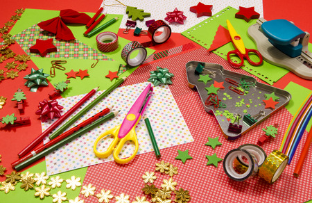 table scraps: Arts and craft supplies for Christmas. Red and green color paper, pencils, different washi tapes, craft scissors, festive xmas supplies for decoration. Stock Photo