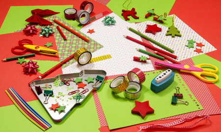 Arts and craft supplies for Christmas. Red and green color paper, pencils, different washi tapes, craft scissors, festive xmas supplies for decoration. Stock Photo