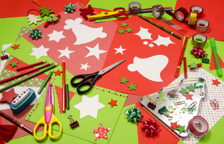 table scraps: Arts and craft supplies for Christmas. Red and green color paper, pencils, different washi tapes, craft scissors, cardboard bell cut and decorations.