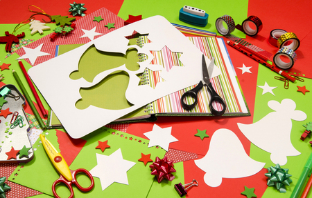craft supplies: Arts and craft supplies for Christmas. Red and green color paper, pencils, different washi tapes, craft scissors, scrapbook agenda, cardboard bell cut and decorations.