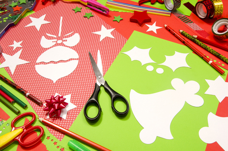 craft supplies: Arts and craft supplies for Christmas. Red and green color paper, pencils, different washi tapes, craft scissors, cardboard bell and Christmas tree ball cut and decorations.