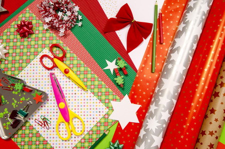 craft supplies: Arts and craft supplies for Christmas. Colorful wrapping paper rolls, pencils, different washi tapes, craft scissors. Wrapping Christmas gifts in colorful paper.