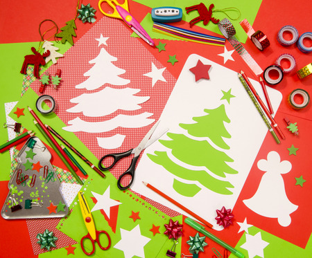 table scraps: Arts and craft supplies for Christmas. Red and green color paper, pencils, different washi tapes, craft scissors, cardboard Christmas tree cut and decorations.