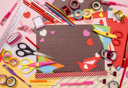 Arts and craft supplies for Saint Valentines.  Color paper, pencils, different washi tapes, craft scissors, hearts supplies for decoration.