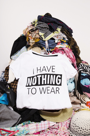 untidy: Big pile of clothes thrown on the ground with a t-shirt saying nothing to wear. Close up on a untidy cluttered wardrobe with colorful clothes and accessories, many clothes and nothing to wear.
