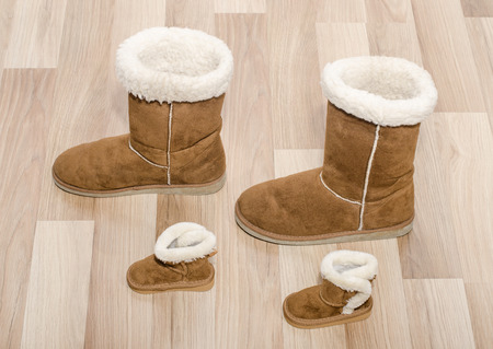similar: Pair of winter woman boots and similar pair of kid boots. Matching big and small boots. Stock Photo