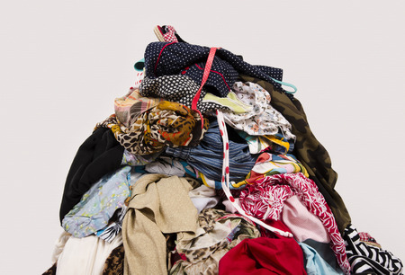 untidy: Close up on a big pile of clothes and accessories thrown on the ground. Untidy cluttered wardrobe with colorful clothes and accessories.