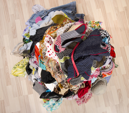 cluttered: Close up on a big pile of clothes and accessories thrown on the ground. Untidy cluttered wardrobe with colorful clothes and accessories.