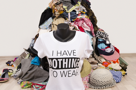 Big pile of clothes thrown on the ground with a t-shirt saying nothing to wear. Untidy cluttered wardrobe with colorful clothes and accessories, many clothes and nothing to wear top on a mannequin.