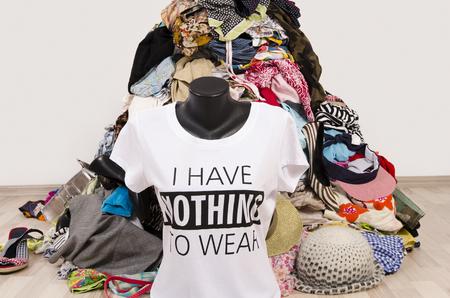 Grote stapel van kleren op de grond gegooid met een t-shirt te zeggen niets te dragen. Slordig rommelig kast met kleurrijke kleding en accessoires, veel kleren en niets om te dragen top op een mannequin.