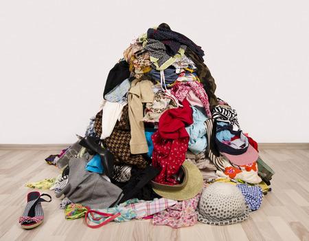 habitacion desordenada: Cierre en una gran pila de ropa y accesorios tirado en el suelo. Armario desordenado desordenado con ropa de colores y accesorios.