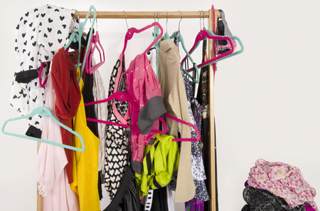 messy clothes: Untidy cluttered woman wardrobe with colorful clothes and accessories. Messy clothes thrown off the hangers and racks and on a shelf.
