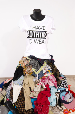 untidy: Big pile of clothes thrown on the ground with a t-shirt saying nothing to wear. Untidy cluttered wardrobe with colorful clothes and accessories, many clothes and nothing to wear top on a mannequin.