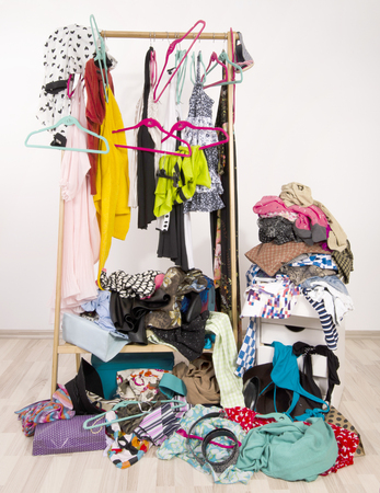 untidy: Untidy cluttered woman wardrobe with colorful clothes and accessories. Messy rack of clothes and hangers with a big pile thrown on the ground.