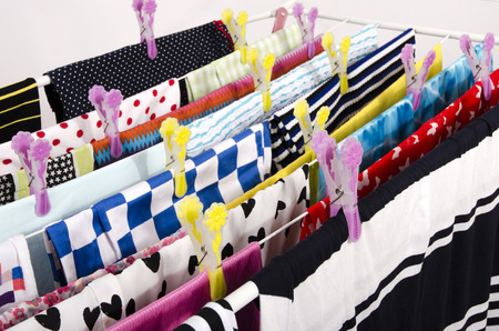 clothes pins: Colorful clothes hanging on a clothes horse to dry. Fresh laundry arranged on a rack with clothes pins.