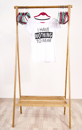 Kast met een leeg rek met merken om t-shirt te dragen. Lege dressing kast met een t-shirt en veel lege hangers.