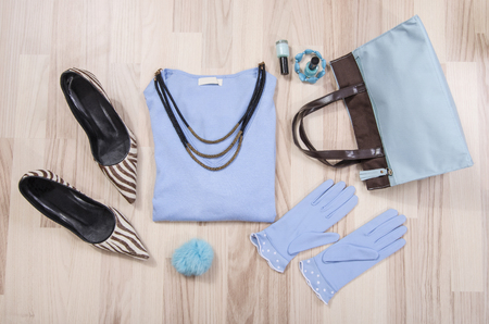 lied: Winter sweater and accessories arranged on the floor. Woman blue and brown accessories, high heels, necklace and gloves lied down. Stock Photo