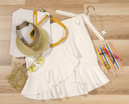 Biała spódnica z ruframi i akcesoriami rozmieszczonymi na podłodze. Spódnica kobiety z dodatkami, torebką, okularami przeciwsłonecznymi, osłoną i paznokciem.