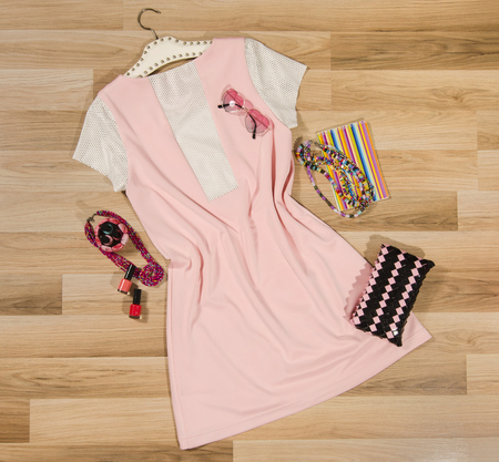 Pink dress with white mesh leather and accessories arranged on the floor. Woman dress with accessories, purse, heart sunglasses and necklace. Stock Photo