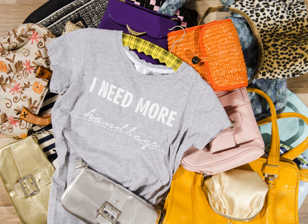 untidy: Big pile of colorful woman bags. Untidy stack of purses thrown on the ground with a t-shirt saying I need more handbags.