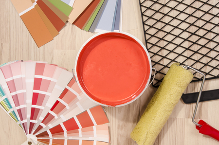 red paint roller: Coral red paint can. Samples with different shades of red and can of red paint with paint roller and accessories. Swatches and paint on the floor.