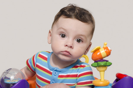 six month old: Cute baby boy sitting and playing with toys. Adorable six month old child happy looking curious. Stock Photo