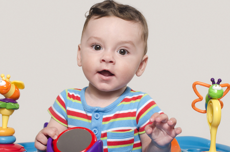 six month old: Cute baby boy sitting and playing with toys. Adorable six month old child happy smiling. Stock Photo