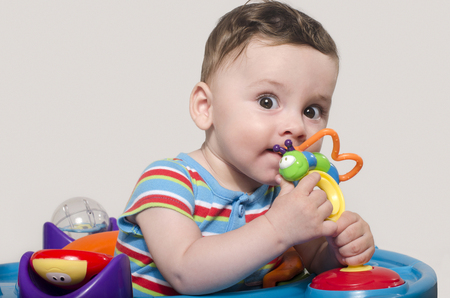 six month old: Cute baby boy sitting and playing with toys. Adorable six month old child chewing a toy. Baby teething.